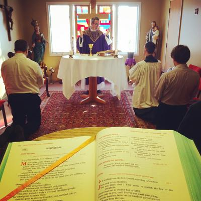 Residents kneel as Father Coffas celebrates Mass in the chapel at Becket Hall.
