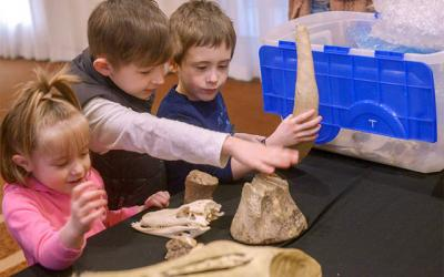 <p>Children look at dinosaur fossils before a presentation by Catholic paleontologist Peter Dodson at Auburn's Hilton Garden Inn March 30. (Courier photo by John Haeger)  </p>