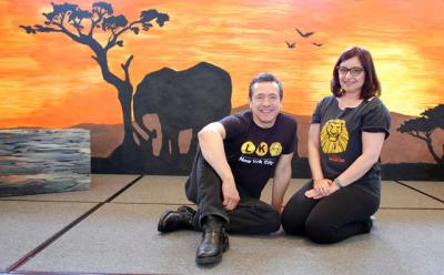 """Enrique Segura, a Broadway actor, and his wife, Kristi, a choreographer, pose on the set of """"The Lion King Jr."""" in early May at the School of Sacred Heart St. Francis de Sales in Bennington, Vt. """"The Lion King Jr.,"""" a 60-minute adaptation of the show about love and redemption, was created especially for the strengths and skill level of middle- school students."""