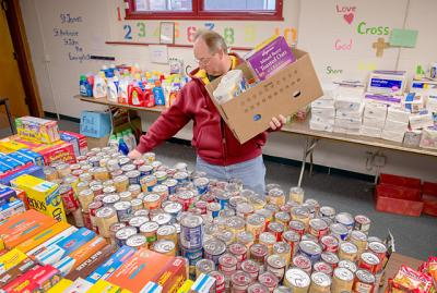 Mark Messmer loads a Christmas basket with supplies for a needy family at Rochester's Peace of Christ Parish Dec. 12.