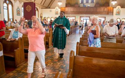 <p>Father John Gathenya processes into St. Alphonsus Church in Auburn for the 10:15 a.m. Mass July 28. On June 25, St. Alphonsus clustered with Auburn&rsquo;s Holy Family and Sacred Heart parishes and St. Ann Parish in Owasco. (Courier photo by John Haeger)  </p>