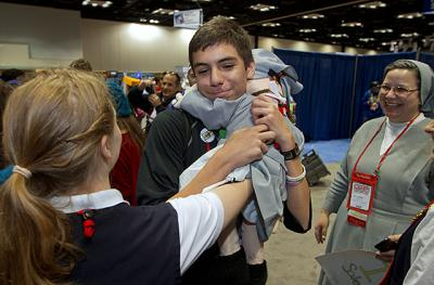 """Tyler Ray, 14, from St. Rita Church in Webster hugs Sister Marianette before hugging her handler, Sister Kelly Schuster, who is based out of New Jersey with the Salesians of Don Bosco. Ray was walking around NCYC with a sign that read """"Free Hugs."""""""