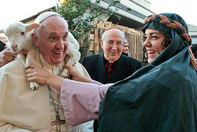 A woman dressed as a character from a Nativity scene puts a lamb around the neck of Pope Francis as he arrives to visit the Church of St. Alfonso Maria dei Liguori in Rome Jan. 6.