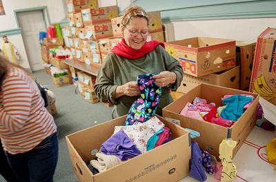 Aira Morales organizes donated clothing at Rochester's Our Lady of the Americas Church Nov. 26. The clothing will be included, along with food, toys and household items, in baskets that are given to needy families before Christmas.