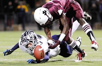 """Aquinas' Jahmahl Pardner reaches for a loose ball after Whitesboro's Connor Passalacqua (left) fumbled during the Class A state semifinal game Nov. 19. (<a href=""""http://catholiccourier.smugmug.com/Other/2010-Aquinas-football-state/14794935_SGoSu#1103400105_kDDPE"""" target=""""_blank"""">Click  here</a> to view more photos from this event and/or buy prints.)"""