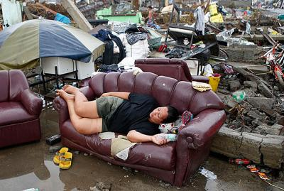 A typhoon victim rests on a sofa amid the ruins of her family's home on the central Philippine island of Leyte. Aid agencies faced challenges getting food and water to the hundreds of thousands of Filipinos affected by Super Typhoon Haiyan.