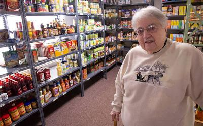 <p>Teresa Quinzi-Willette, director of the East Rochester Community Resource Center, poses in the center&rsquo;s food pantry area Dec. 19. (Courier photo by John Haeger)  </p>