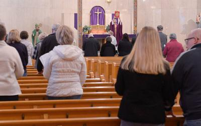 <p>Father Justin Miller elevates the Book of the Gospels during the 10 a.m. Mass at St. Hyacinth Church in Auburn March 14. (Courier photo by John Haeger)  </p>