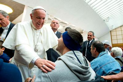 Pope Francis greets people in wheelchairs during a meeting with UNITALSI, an Italian Catholic association for the transportation of sick people to Lourdes and other Marian shrines, in Paul VI hall at the Vatican Nov. 9.