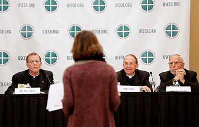 A reporter asks a question during a news conference at the U.S. bishops' annual fall meeting in Baltimore Nov. 11. Pictured from left is Bishop John C. Wester of Salt Lake City, Utah, Archbishop William E. Lori of Baltimore and Bishop Gerald F. Kicanas of Tucson, Ariz.