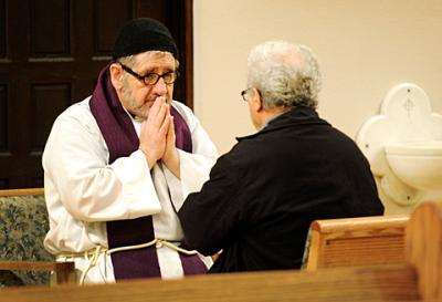 Father Ray Fleming (left) listens to a penitent's confession during a 2012 Ash Wednesday service at Rochester's St. Monica Church.