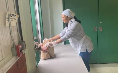 <p>Deb Best hands out to-go meals at the door of Elmira Community Kitchen.  </p>