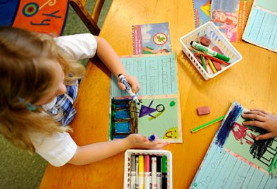 Kindergartner Laura Manjerovic works on her drawing and writing skills June 12 at St. Louis School in Pittsford.