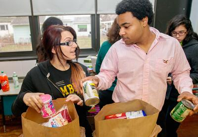 Seventeen-year-olds Toni Peggi (left) and Robert Dolemann assemble food bags for needy families Dec. 8, 2013, at St. Charles Borromeo Church in Greece.