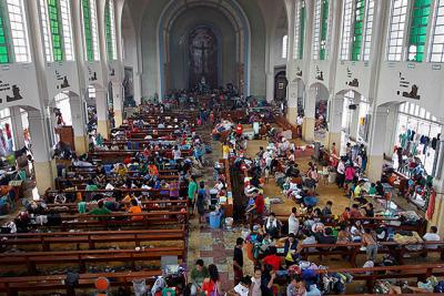 Residents seek refuge inside a Catholic church converted into an evacuation center Nov. 10 after Super Typhoon Haiyan battered Tacloban, Philippines. The typhoon, one of the strongest storms in history, is believed to have killed tens of thousands, but aid workers were still trying to reach remote areas.