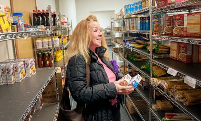 Kim Whaley gathers items from the client-choice food pantry during a visit to Catholic Family Center's Community Resource Services in November 2013.