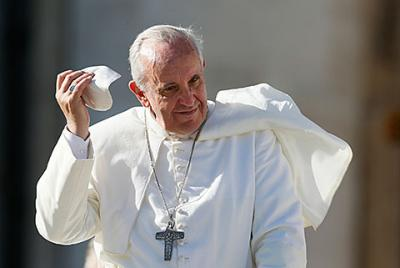 Pope Francis takes off his zucchetto as he leaves his general audience in St. Peter's Square at the Vatican Nov. 6.
