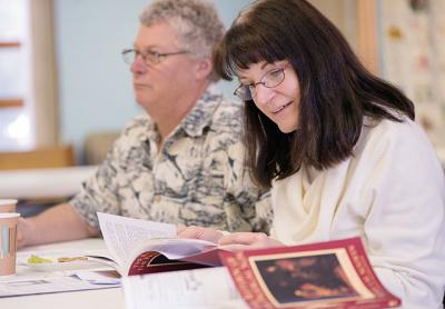 Diana Guilford thumbs through The Return of the Prodigal Son: A Story of Homecoming during a Feb. 21 book discussion at St. Bridget Church in East Bloomfield.