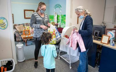 <p>Jackie Bach picks up clothing and supplies from volunteer Kim Keenan at the Women&rsquo;s Care Center in Rochester Sept. 30. (Courier photo by Jeff Witherow)  </p>