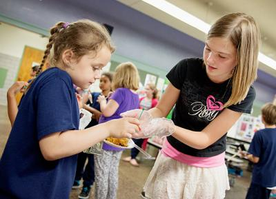 Sixth-grader Danielle Stein (right) hands a crepe to second-grader Eva Meddaugh during a June 13 'World Bazaar' at Holy Cross School in Rochester. The diocesan Department of Catholic Schools is spreading the word about local Catholic schools in new ways.