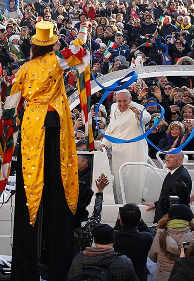 Pope Francis passes a circus performer on stilts as he arrives to lead his general audience in St. Peter's Square at the Vatican Jan. 8.