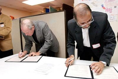 Bishop Clark and Dr. Muhammad Shafiq sign an agreement between the Catholic and Muslim faith communities May 5, 2003
