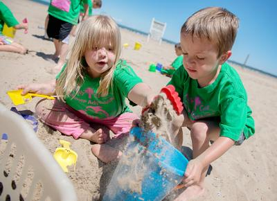Four-year-olds Hailey Case (left) and Noah Boothby play in the sand July 10 during a trip to Ontario Beach Park for participants in the Holy Cross Summer Adventure day camp.