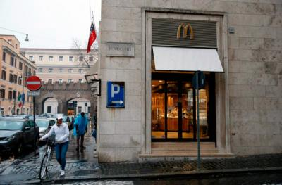 "A worker crosses the street with her bike outside the newly opened McDonald's near the Vatican Jan. 12. The McDonald's will collaborate with Italian aid organization, ""Medicinia Solidale,"" and the papal almoner's office to help feed the poor and homeless around the Vatican."