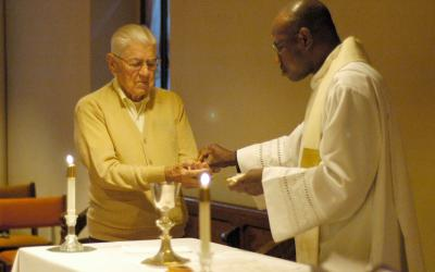 Joe Monahan, 87, receives Communion from Father Felix Dalimpuo during daily Mass Sept. 23 at St. Michael Parishin Newark. Monahan volunteers at the parish as an altar server.