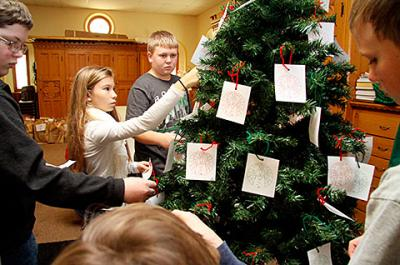 Faith-formation students Dylan Wilder (from left), Celia Mattie, Aiden Tardif and Ryan Gilbert decorate a giving tree at Auburn's Holy Family Church Nov. 24. (Courier photo by Devon Roblee)