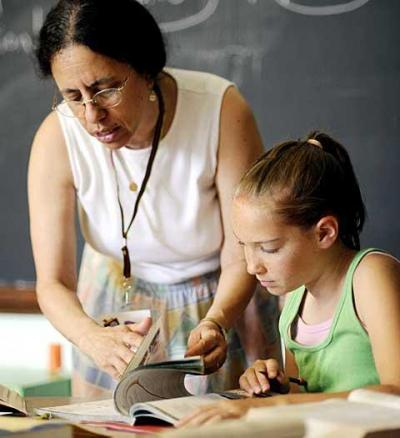 Religious-education teacher Donna Schwartz helps 11-year-old Meghan Keyes with a lesson July 19 at St. Charles Borromeo Church in Greece. Meghan has nystagmus, a vision-impairing condition typified by involuntary eye movement.