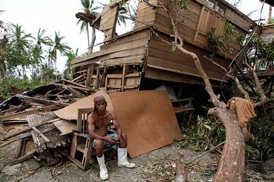 A man in Cebu, Philippines, takes a break from salvaging reusable wood from his destroyed house Nov. 11 after Super Typhoon Haiyan hit Nov. 8. The typhoon, one of the strongest storms in history, is believed to have killed tens of thousands, but aid workers were still trying to reach remote areas.