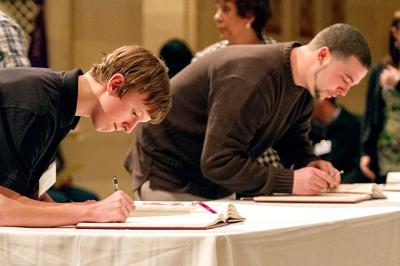 Catechumens sign their names in the Book of the Elect during the Rite of Election March 9 at Sacred Heart Cathedral in Rochester.