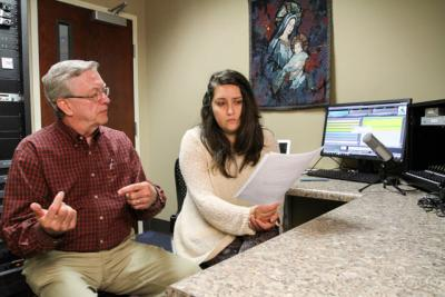 Ken Chivers offers some suggestions Oct. 19 to Ablaze Radio volunteer Valeria Longhi just before she prepares to record a radio promotion spot in Duluth, Ga. Ablaze, a low-power station, is the newest Catholic radio station on the air in the Atlanta Archdiocese.