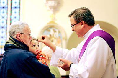 Quinn Dale, 3, receives ashes from Deacon Peter Dohr as Quinn's grandfather, Gary Brundage, looks on at St. Rose Church in Lima Feb. 13, 2013.