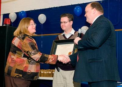 In 2008, All Saints Academy Principal Rose Ann Ewanyk receives congratulations on the school's accreditation from Corning Mayor Tom Reed (right) as Deacon Dean Condon looks on.