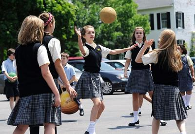 Sixth-graders Hannah Gilges (center) and Adrienne Porter (right) join classmates in a game during recess June 8 at St. Mary School in Canandaigua.