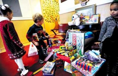 St. Ann School in Hornell held a new toy drive for needy kids in December. Above, students Josephina Lichioveri (from left), Pierce Young and Genevieve Kemnitzer look through the donated toys Dec. 10.