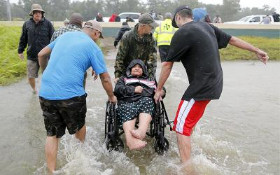 <p>An elderly woman in a wheelchair is rescued by volunteers from the floodwaters of Tropical Storm Harvey Aug. 28 in Houston. </p>