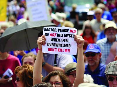 A woman holds up a sign during a rally against assisted suicide in 2016 on Parliament Hill in Ottawa, Ontario.