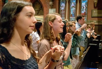 Students hold hands while praying the Our Father during Mass in Sage Chapel on the campus of Ithaca's Cornell University Aug. 31, 2014.