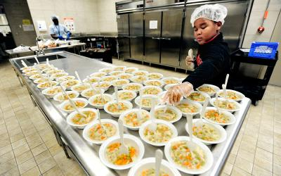 Nine-year-old Elliot Jerry puts out chicken and rice soup for hungry kids at the Thomas P. Ryan Community Center in Rochester Sept. 22. (Courier photo by Mike Crupi)