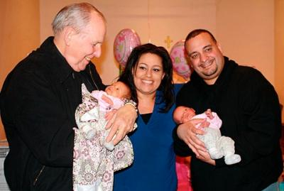Bishop Matthew H. Clark holds Melina Sotomayor as Amanda and David Sotomayor look on during a baby shower at Holy Apostles Parish in Rochester. The bishop prayed for the Sotomayor family before Melina and her twin sister, Olivia (right), were born.