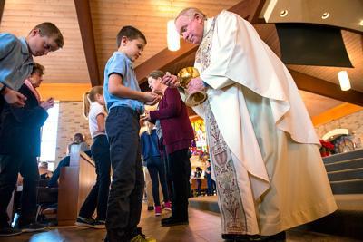 Evan Klimasewski receives Communion from Father James Schwartz during a First Friday Mass at Penfield's St. Joseph Church Jan. 6.