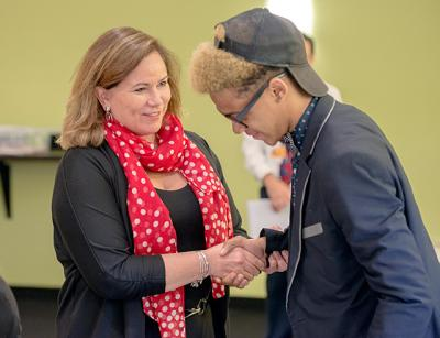 Louise Vella, director of Workforce and Leadership Development at Unity Health System, shakes hands May 31 with Patrick Quick, 16, a junior at School Without Walls, after Patrick told Vella and his classmates in Hillside's Youth Employment Training Academy why he should be hired.