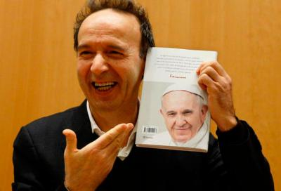 """Italian actor Roberto Benigni holds a copy of the book, """"The Name of God Is Mercy,"""" during its presentation to journalists in Rome Jan. 12. The book is compiled from an interview Pope Francis did with Italian journalist Andrea Tornielli."""