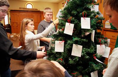 Faith-formation students Dylan Wilder (from left), Celia Mattie, Aiden Tardif and Ryan Gilbert decorate a giving tree at Auburn's Holy Family Church in this November 2013 photo.