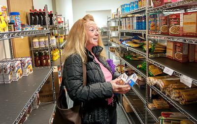 Kim Whaley gathers items from the client-choice food pantry during a Nov. 22 visit to Catholic Family Center's Community Resource Services in Rochester.