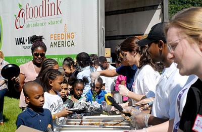 Children line up for a Freshwise meal outside The Community Place during a Foodlink summer meals outreach event June 2.