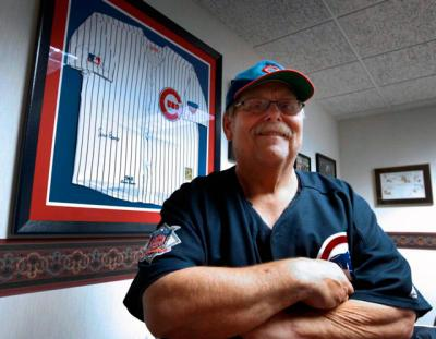 Father John W. Clemens, pastor of Our Lady of Hope Church in Rosemont, Ill., poses for a photo Oct. 27 near his jersey signed by Chicago Cubs legend Ernie Banks.